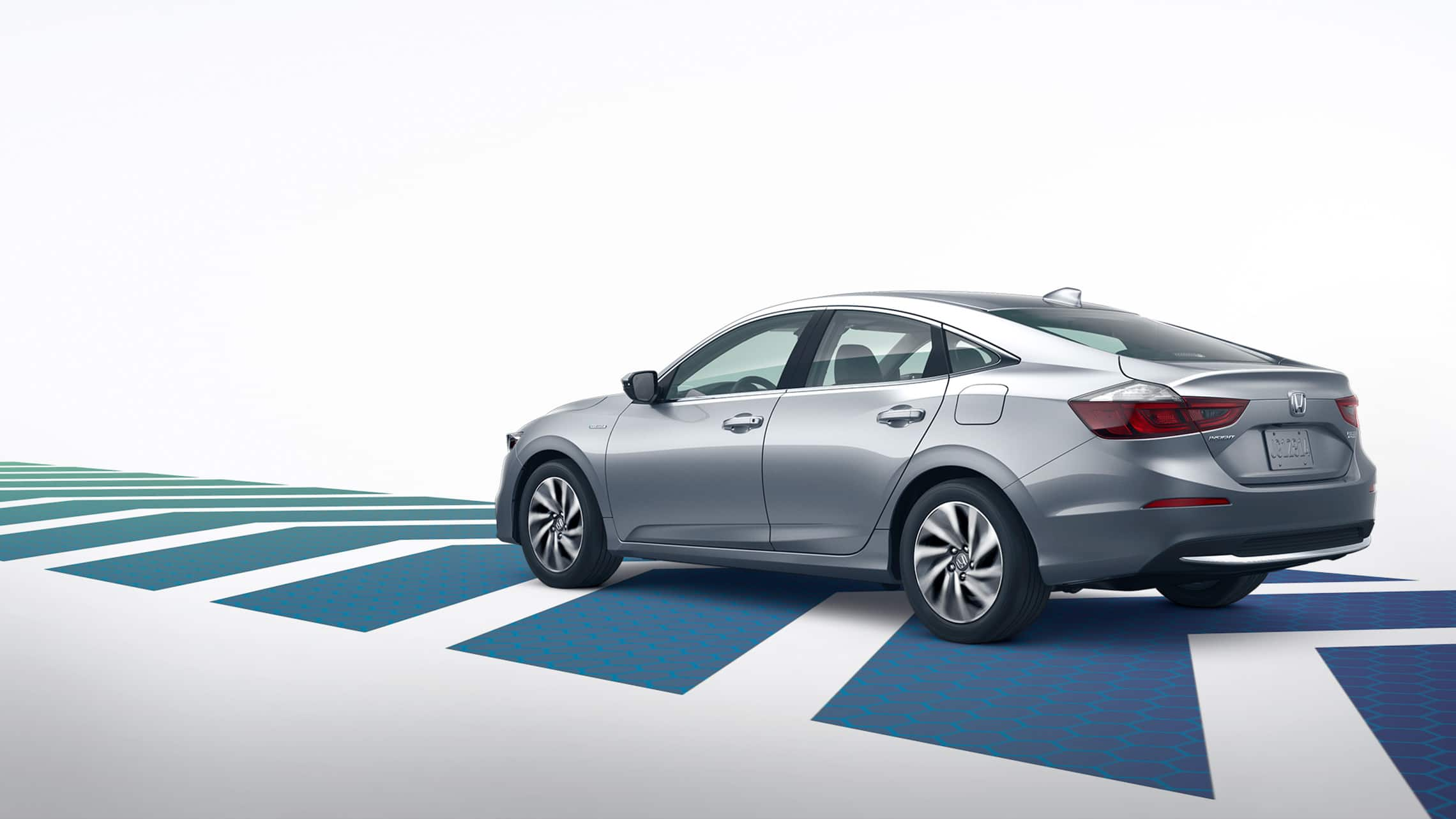 Rear driver-side view of 2021 Honda Insight Touring in Lunar Silver Metallic with MPG and range graphic overlay.